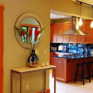 オレンジカウンティの中サイズのモダンスタイルのおしゃれなキッチン (青いキッチンパネル、ガラスタイルのキッチンパネル、シェーカースタイル扉のキャビネット、中間色木目調キャビネット、人工大理石カウンター、シルバーの調理設備、淡色無垢フローリング、ベージュの床) の写真