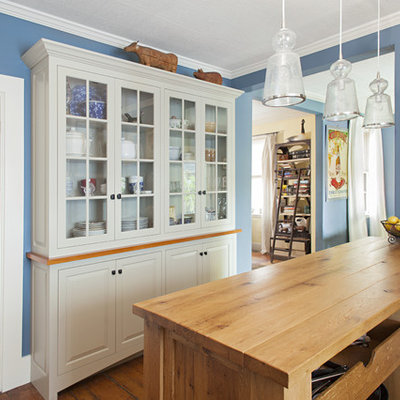 Open concept kitchen - traditional open concept kitchen idea in Boston with glass-front cabinets, gray cabinets and wood countertops
