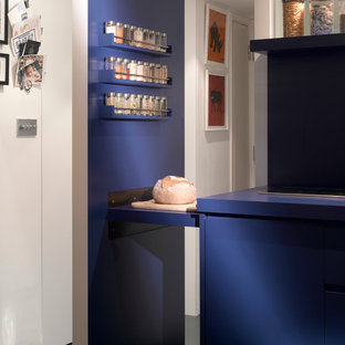 Inspiration for a small contemporary open plan kitchen in London with a drop-in sink, flat-panel cabinets, blue cabinets, stainless steel appliances and ceramic floors.