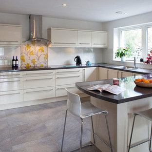 Small contemporary u-shaped kitchen in Cornwall with an integrated sink, flat-panel cabinets, white cabinets, solid surface benchtops, white splashback, ceramic floors and a peninsula.