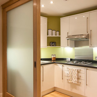 Inspiration for a small contemporary kitchen in Edinburgh with flat-panel cabinets, white cabinets and medium hardwood flooring.