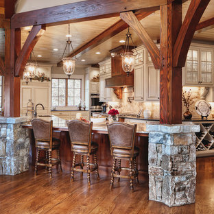 Rustic eat-in kitchen remodeling - Inspiration for a rustic l-shaped medium tone wood floor and brown floor eat-in kitchen remodel in Other with an undermount sink, raised-panel cabinets, gray cabinets, beige backsplash, paneled appliances, an island and gray countertops