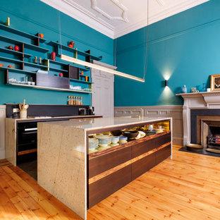 Idée de décoration pour une cuisine américaine parallèle design de taille moyenne avec un évier 1 bac, un placard à porte plane, des portes de placard en bois sombre, un plan de travail en granite, une crédence noire, un électroménager noir, un sol en ardoise, un îlot central et un sol gris.