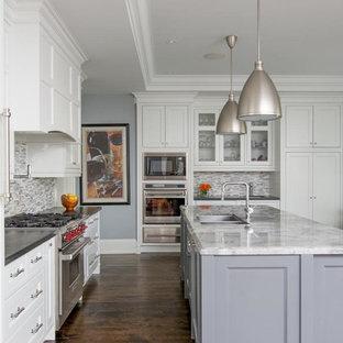 Cette photo montre une cuisine parallèle chic avec un évier 2 bacs, un placard avec porte à panneau encastré, des portes de placard blanches, une crédence grise et un électroménager en acier inoxydable.