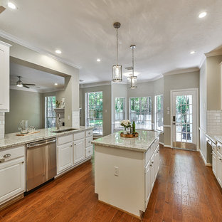This is an example of a medium sized classic u-shaped kitchen/diner in Houston with a submerged sink, louvered cabinets, white cabinets, granite worktops, white splashback, metro tiled splashback, stainless steel appliances, medium hardwood flooring, an island, orange floors and white worktops.
