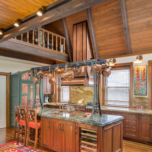 This is an example of a large country l-shaped open plan kitchen in Kansas City with a double-bowl sink, beaded inset cabinets, medium wood cabinets, granite benchtops, brown splashback, stone slab splashback, stainless steel appliances, medium hardwood floors and with island.