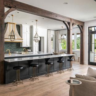 Klassisk inredning av ett stort vit vitt kök, med mellanmörkt trägolv, skåp i shakerstil, vita skåp, marmorbänkskiva, grönt stänkskydd, flera köksöar och brunt golv
