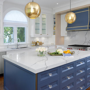 Mid-sized trendy l-shaped medium tone wood floor and brown floor eat-in kitchen photo in Toronto with a double-bowl sink, recessed-panel cabinets, white cabinets, quartz countertops, white backsplash, marble backsplash, stainless steel appliances, an island and white countertops