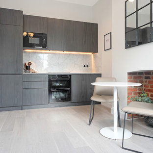 This is an example of a contemporary single-wall kitchen/diner in London with flat-panel cabinets, grey cabinets, white splashback, black appliances, no island and grey floors.