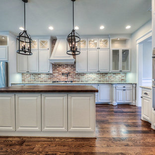 Inspiration for a large arts and crafts galley open plan kitchen in Houston with a farmhouse sink, raised-panel cabinets, white cabinets, wood benchtops, red splashback, stone tile splashback, stainless steel appliances, dark hardwood floors and with island.