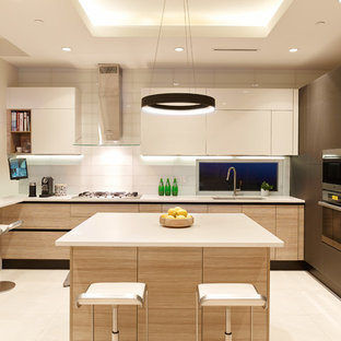 Inspiration for a small contemporary u-shaped ceramic floor kitchen remodel in Vancouver with a double-bowl sink, flat-panel cabinets, quartz countertops, white backsplash, glass tile backsplash, paneled appliances, an island and white cabinets