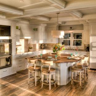 ミネアポリスの大きいトラディショナルスタイルのおしゃれなキッチン (白いキャビネット、アンダーカウンターシンク、インセット扉のキャビネット、木材カウンター、ベージュキッチンパネル、ボーダータイルのキッチンパネル、パネルと同色の調理設備、無垢フローリング、茶色い床) の写真
