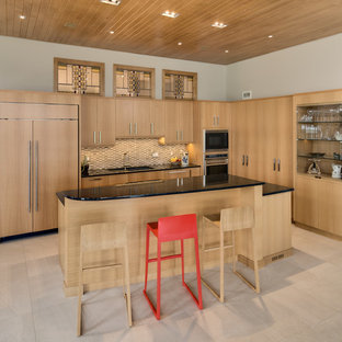 Design ideas for a contemporary l-shaped open plan kitchen in Other with flat-panel cabinets, light wood cabinets, granite benchtops, beige splashback, glass tile splashback, panelled appliances, ceramic floors and with island.
