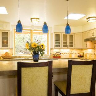 アルバカーキのサンタフェスタイルのおしゃれなアイランドキッチン (シェーカースタイル扉のキャビネット、タイルカウンター、石タイルのキッチンパネル、シルバーの調理設備の、磁器タイルの床) の写真