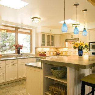 アルバカーキのサンタフェスタイルのおしゃれなアイランドキッチン (シェーカースタイル扉のキャビネット、タイルカウンター、石タイルのキッチンパネル、シルバーの調理設備、磁器タイルの床) の写真