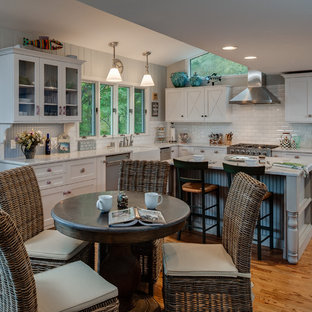 Beach style eat-in kitchen photos - Eat-in kitchen - beach style l-shaped eat-in kitchen idea in Other with a farmhouse sink, recessed-panel cabinets, white cabinets, marble countertops, white backsplash, subway tile backsplash and stainless steel appliances