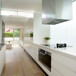 Photo of a contemporary galley kitchen in Sydney with an undermount sink, flat-panel cabinets, white cabinets, window splashback, black appliances, light hardwood floors, with island, beige floor and white benchtop.