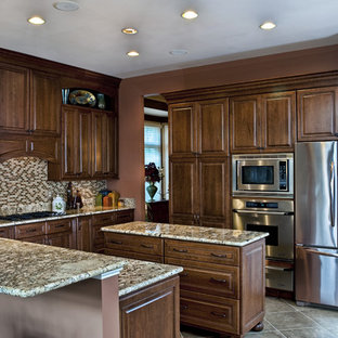 Inspiration for a mid-sized timeless u-shaped ceramic floor eat-in kitchen remodel in DC Metro with stainless steel appliances, granite countertops, raised-panel cabinets, medium tone wood cabinets, multicolored backsplash, mosaic tile backsplash, an undermount sink and an island