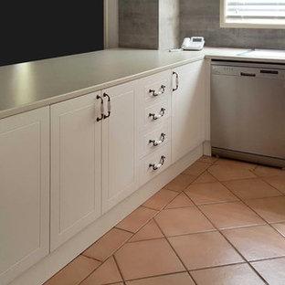 シドニーの大きいコンテンポラリースタイルのおしゃれなキッチン (ダブルシンク、ベージュのキャビネット、ラミネートカウンター、セラミックタイルのキッチンパネル、シルバーの調理設備の、インセット扉のキャビネット、グレーのキッチンパネル、テラコッタタイルの床、赤い床) の写真