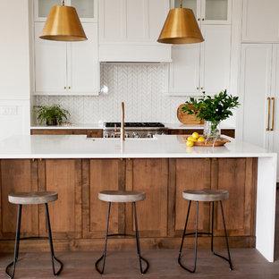 ボイシの中サイズのカントリー風おしゃれなキッチン (エプロンフロントシンク、シェーカースタイル扉のキャビネット、中間色木目調キャビネット、クオーツストーンカウンター、白いキッチンパネル、モザイクタイルのキッチンパネル、シルバーの調理設備、無垢フローリング、茶色い床、白いキッチンカウンター) の写真