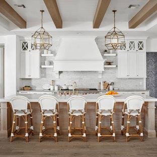Große Country Küche mit Landhausspüle, weißen Schränken, Quarzwerkstein-Arbeitsplatte, Rückwand aus Marmor, hellem Holzboden, Kücheninsel, beigem Boden, grauer Arbeitsplatte, Schrankfronten im Shaker-Stil, Küchenrückwand in Weiß und Küchengeräten aus Edelstahl in Phoenix