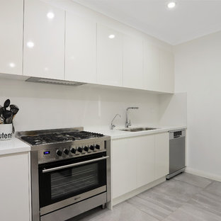 Photo of a mid-sized modern l-shaped eat-in kitchen in Sydney with an undermount sink, flat-panel cabinets, white cabinets, quartz benchtops, white splashback, slate splashback, stainless steel appliances, porcelain floors, no island, grey floor and white benchtop.
