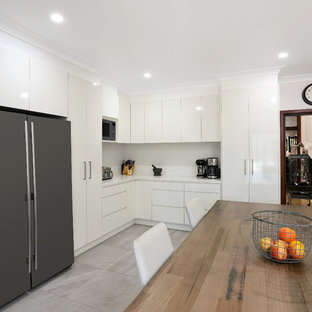 Inspiration for a mid-sized modern l-shaped eat-in kitchen in Sydney with an undermount sink, flat-panel cabinets, white cabinets, quartz benchtops, white splashback, slate splashback, stainless steel appliances, porcelain floors, no island, grey floor and white benchtop.