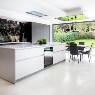 This is an example of an expansive contemporary galley kitchen/diner in London with an island, flat-panel cabinets, black cabinets, black splashback, integrated appliances, white floors and white worktops.