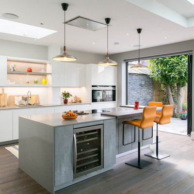 Large trendy galley medium tone wood floor and brown floor eat-in kitchen photo in London with an island, an undermount sink, flat-panel cabinets, white cabinets, white backsplash, stainless steel appliances and gray countertops