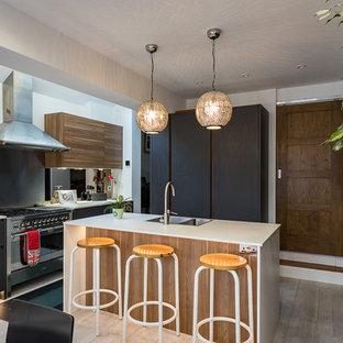Photo of a medium sized world-inspired open plan kitchen in London with flat-panel cabinets, grey cabinets, laminate countertops, metallic splashback, mirror splashback, stainless steel appliances, light hardwood flooring and an island.