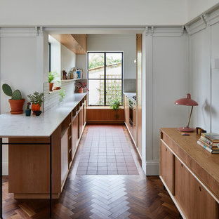 This is an example of a midcentury galley kitchen in London with flat-panel cabinets, medium wood cabinets, white splashback, a breakfast bar and white worktops.