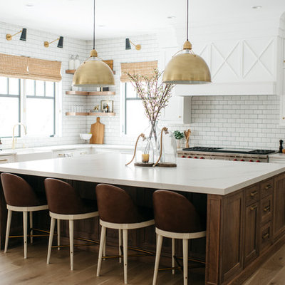 Farmhouse l-shaped medium tone wood floor and brown floor eat-in kitchen photo in Detroit with a farmhouse sink, shaker cabinets, white cabinets, white backsplash, subway tile backsplash, stainless steel appliances, an island and white countertops
