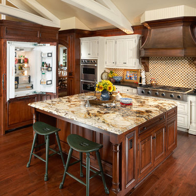 Elegant kitchen photo in Phoenix with raised-panel cabinets, paneled appliances and granite countertops