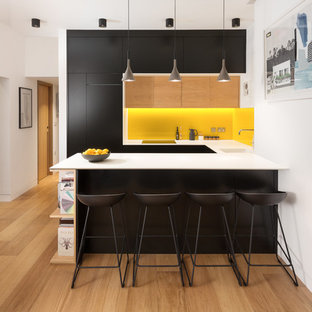 This is an example of a small contemporary u-shaped kitchen in London with a submerged sink, flat-panel cabinets, black cabinets, yellow splashback, light hardwood flooring, a breakfast bar, brown floors and integrated appliances.