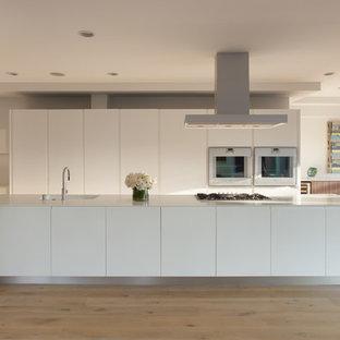Inspiration pour une cuisine américaine parallèle minimaliste avec un évier intégré, un placard à porte plane, des portes de placard blanches, un électroménager blanc, un sol en bois clair et un îlot central.