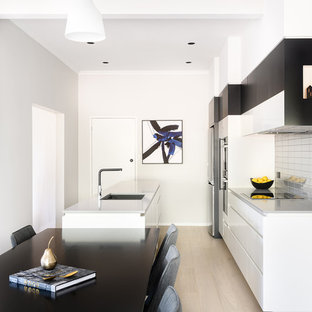 Design ideas for a contemporary galley eat-in kitchen in Hobart with an undermount sink, flat-panel cabinets, white cabinets, grey splashback, stainless steel appliances, light hardwood floors, a peninsula, beige floor and grey benchtop.