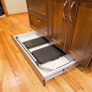 Foto på ett avskilt, mellanstort vintage l-kök, med en undermonterad diskho, släta luckor, bruna skåp, granitbänkskiva, beige stänkskydd, stänkskydd i stenkakel, rostfria vitvaror, ljust trägolv och en köksö
