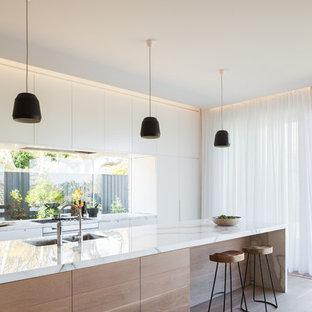 シドニーの北欧スタイルのおしゃれなキッチン (アンダーカウンターシンク、白いキャビネット、大理石カウンター、淡色無垢フローリング、フラットパネル扉のキャビネット、ガラス板のキッチンパネル) の写真