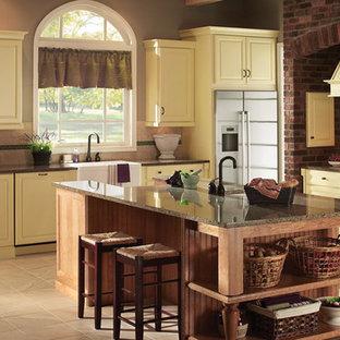 ニューヨークの中サイズのサンタフェスタイルのおしゃれなキッチン (エプロンフロントシンク、黄色いキャビネット、御影石カウンター、ベージュキッチンパネル、セラミックタイルのキッチンパネル、シルバーの調理設備、セラミックタイルの床、レイズドパネル扉のキャビネット) の写真
