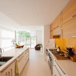 オタワの中くらいのモダンスタイルのおしゃれなキッチン (アンダーカウンターシンク、フラットパネル扉のキャビネット、淡色木目調キャビネット、人工大理石カウンター、オレンジのキッチンパネル、木材のキッチンパネル、磁器タイルの床、白い床、白いキッチンカウンター) の写真
