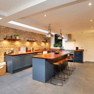 Inspiration for a large country l-shaped kitchen in London with a belfast sink, recessed-panel cabinets, blue cabinets, wood worktops, stainless steel appliances, an island, grey floors and brown worktops.