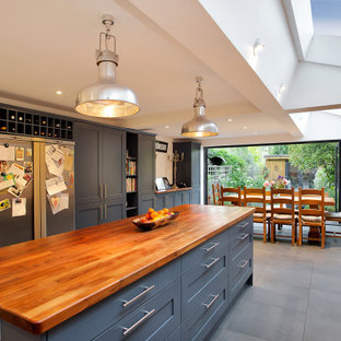 Inspiration for a traditional galley kitchen/diner in London with shaker cabinets, grey cabinets, wood worktops, an island, grey floors and brown worktops.