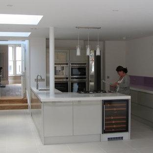 ロンドンのヴィクトリアン調のおしゃれなキッチン (ドロップインシンク、フラットパネル扉のキャビネット、グレーのキャビネット、人工大理石カウンター) の写真