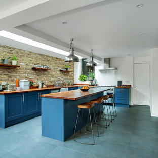Large traditional l-shaped kitchen/diner in London with a belfast sink, shaker cabinets, blue cabinets, wood worktops, stainless steel appliances, ceramic flooring, an island, grey floors, brown worktops, brown splashback and brick splashback.