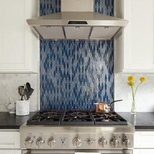 Идея дизайна: линейная кухня среднего размера в классическом стиле с синим фартуком, техникой из нержавеющей стали, обеденным столом, врезной раковиной, фасадами в стиле шейкер, белыми фасадами, столешницей из оникса, фартуком из каменной плитки и светлым паркетным полом без острова