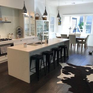 メルボルンの中くらいのヴィクトリアン調のおしゃれなキッチン (ドロップインシンク、落し込みパネル扉のキャビネット、白いキャビネット、御影石カウンター、白いキッチンパネル、ガラス板のキッチンパネル、黒い調理設備、濃色無垢フローリング、茶色い床、白いキッチンカウンター) の写真