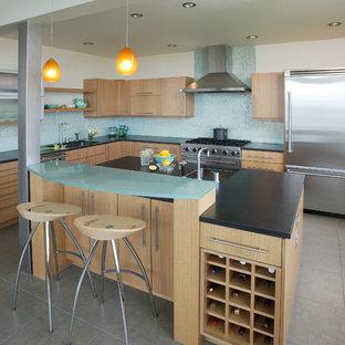 Пример оригинального дизайна: угловая кухня в современном стиле с техникой из нержавеющей стали, стеклянной столешницей, плоскими фасадами, светлыми деревянными фасадами, синим фартуком, бирюзовой столешницей и барной стойкой