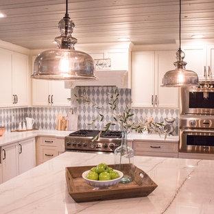 オーランドの小さいカントリー風おしゃれなキッチン (エプロンフロントシンク、落し込みパネル扉のキャビネット、白いキャビネット、珪岩カウンター、マルチカラーのキッチンパネル、ガラスタイルのキッチンパネル、シルバーの調理設備、淡色無垢フローリング、茶色い床、白いキッチンカウンター) の写真
