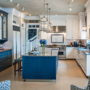Expansive beach style u-shaped open plan kitchen in New York with a drop-in sink, flat-panel cabinets, white cabinets, granite benchtops, beige splashback, stone slab splashback, stainless steel appliances, terra-cotta floors and a peninsula.
