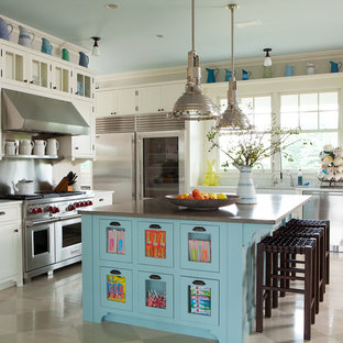 Design ideas for a country kitchen in New York with a belfast sink, glass-front cabinets, soapstone worktops, metallic splashback, stainless steel appliances, travertine flooring and an island.